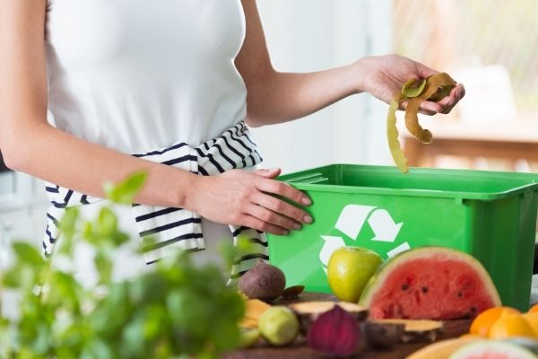 Person placing left over fruits in compost bin