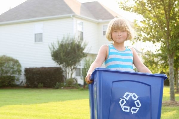 Child near home holding garbage bin with recycle logo