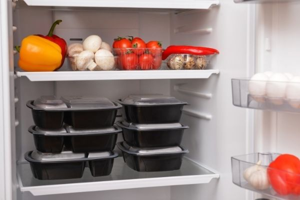 Fridge with plastic food containers and vegetables