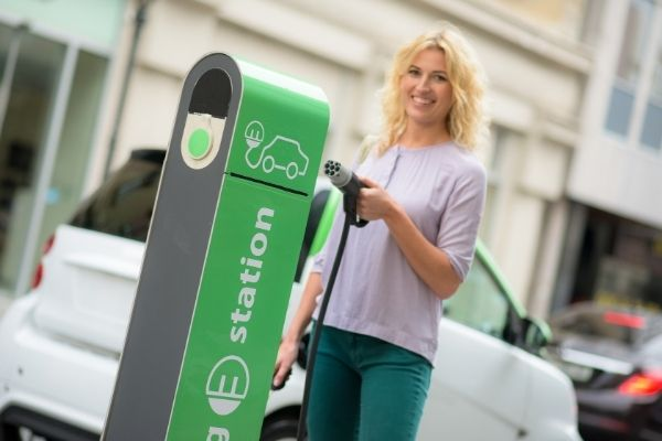 A woman at a charging station for electric cars