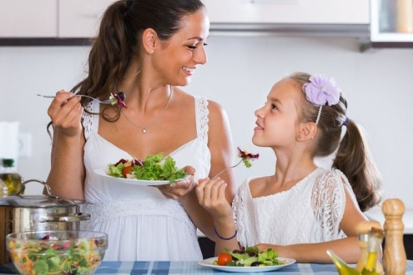 Mom and daughter eating fruit and veggie salad