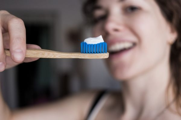 Woman holding a non plastic toothbrush with toothpaste