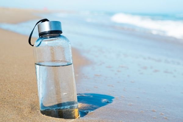 Reusable bottle with water on sand
