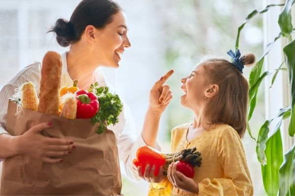 Mother and daughter holding grocery items mostly fruits and vegetables