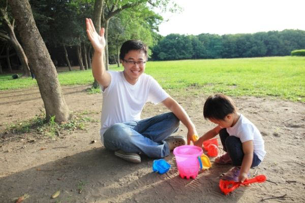 dad and son playing with sand