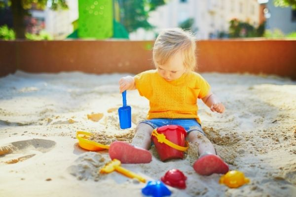 little boy covered in sand while playing on sandbox