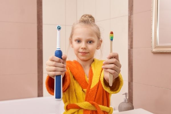 little girl holding an electric toothbrush and a bamboo toothbrush