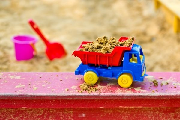 toy truck filled with sand on sandbox