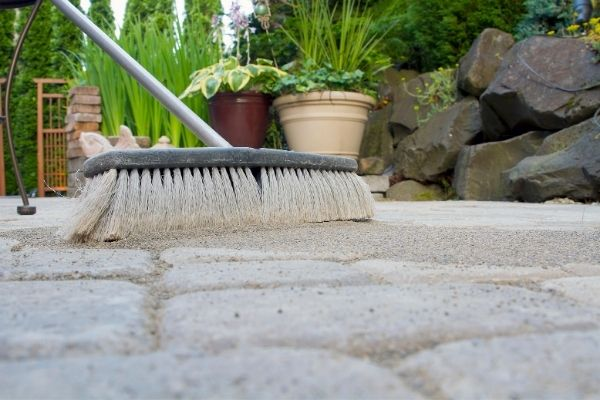using a broom to scatter sand between pavements in the garden