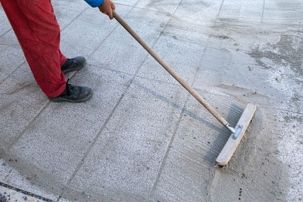 worker sweeping polymeric sand