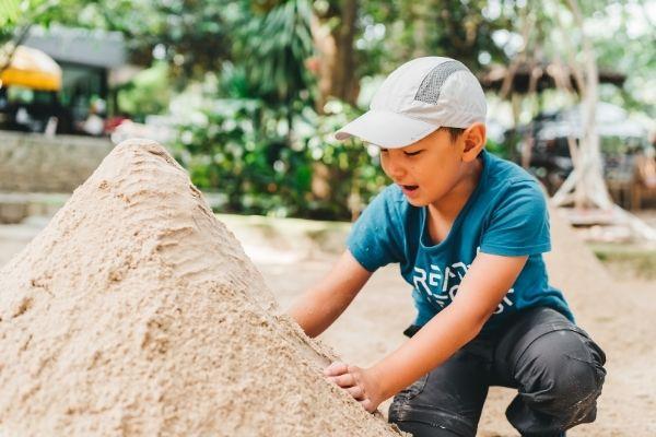 young boy playing with mountain of play sand at home