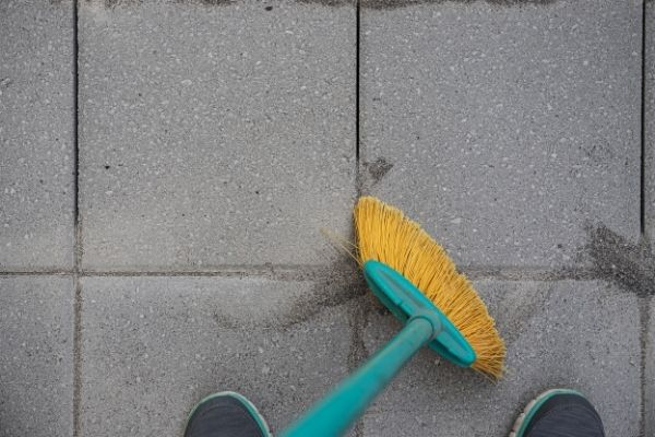brushing jointing sand in pavers with push broom