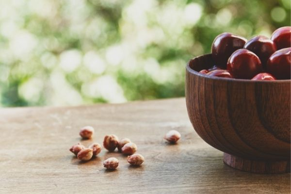cherry and cherry pits on wooden table