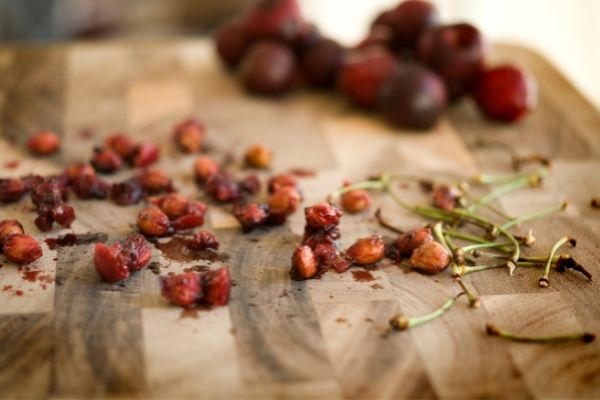 cherry, cherry pits and stems on a table