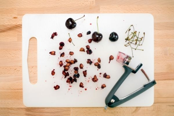 cherry pits on white cutting board