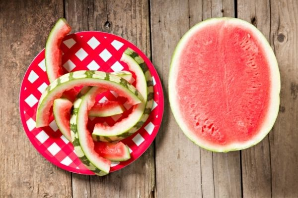 half a watermelon and watermelon rinds on a plate