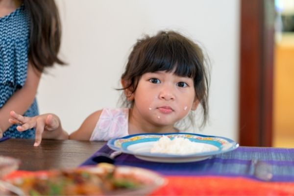 young child eating white rice