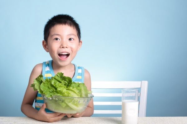 kid with green vegetable