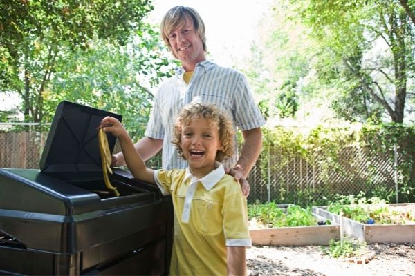 parent and child using outdoor compost bin