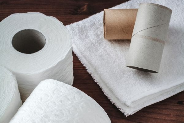 roll of tissues and toilet paper rolls on white towel